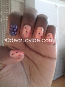 """1. Base coat 2. Two coats of Peachy Nail polish (or colour of choice) 3. Use dotting tool/brush to dot on colours of choice in a """"flower"""" shape. I used a pastel blue, purple, hot pink & black. 4. Once dry add top coat for shine. For Index finger: 1. Base coat 2. Two coats of shimmery purple. 3. Use dotting tool to create flowers. I used pastel blue and pink petals. 4. Once dry add top coat for shine."""